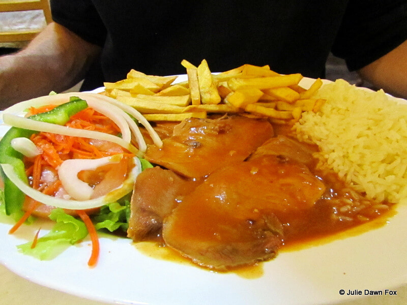sliced pork with rice, chips and salad