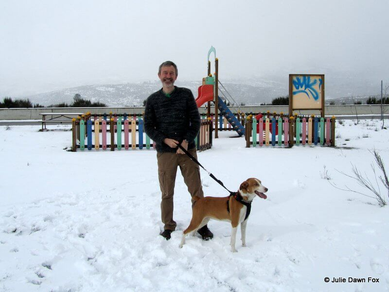 man and dog standing in the snow
