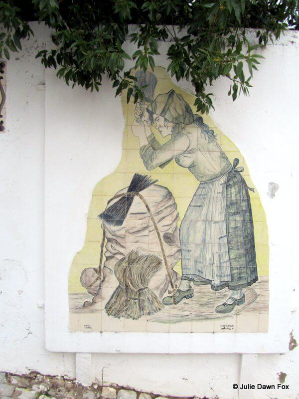 Handpainted ceramic panel depicting a woman beating esparto grass on a stone in Alte, Algarve, Portugal