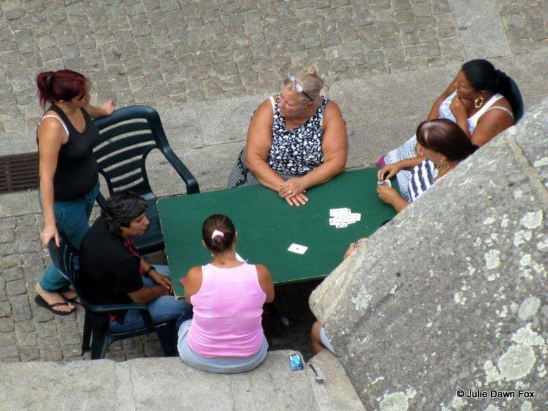 Ladies playing cards in the street below Porto cathedral.