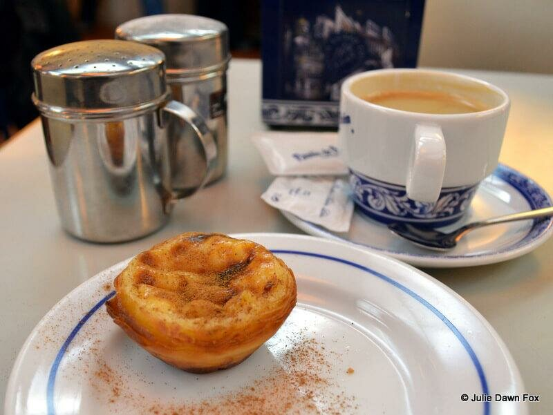 A custard tart dusted in cinnamon powder and a cup of milky coffee