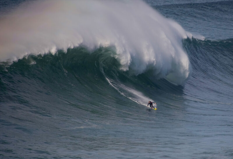 Man surfing huge wave in Nazare, Portugal