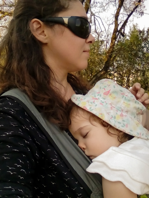 Baby asleep in her babywearing harness