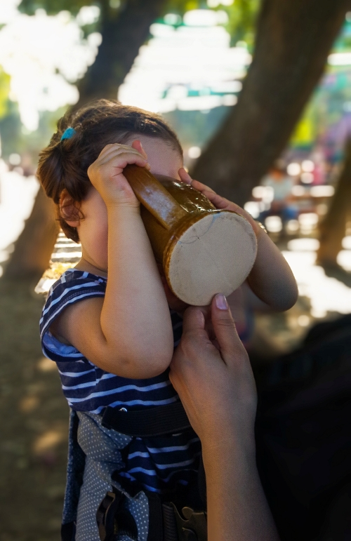 Little girl drinks from a ceramic mug at a festival in Portugal