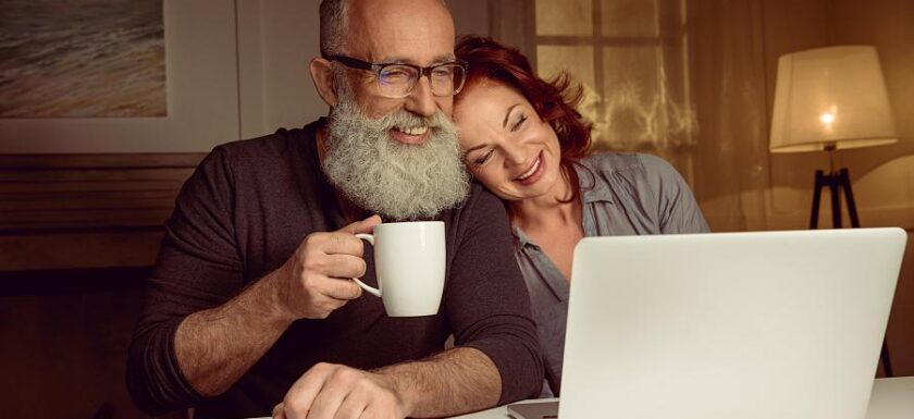 Couple watching online expereinces on a laptop. Possibly virtual tours in Portugal