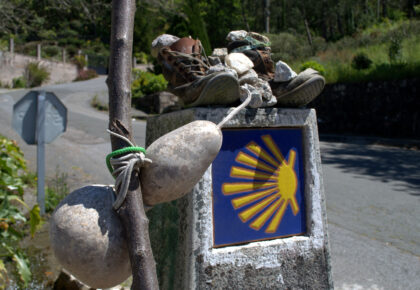 Walking boots,gourd and shell on sign of Camino.
