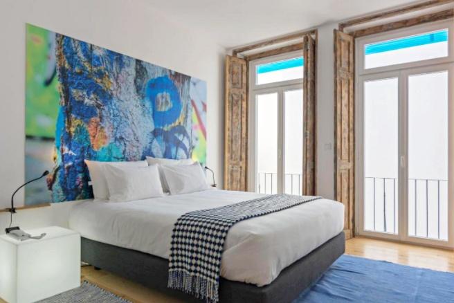 Bed with colourful art headboard at Chiado Arty Flats, Lisbon
